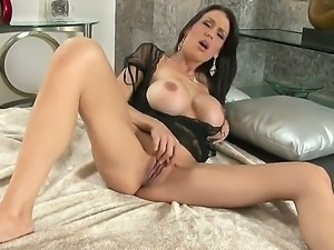 Arousing dark haired McKenzie Lee reveals her melons as she fingers her...