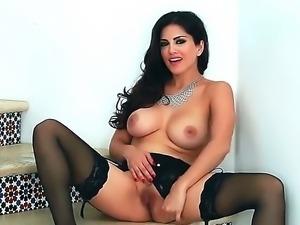 Gorgeous brunette Sunny Leone likes posing while gently fingering her wet vag
