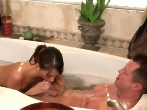 Gorgeous brunette therapist gives oral massage in the bath